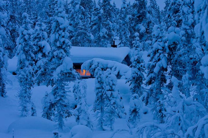Wilderness cabin in the snow covered forest. Inside warm and cosy.