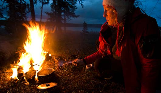 Stina vid lägerelden under en kanottur i Svenska Lappland