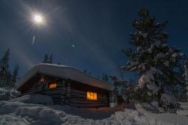 Winter time in Jokkmokk and full moon over a timber hut on a dog sledding tour.