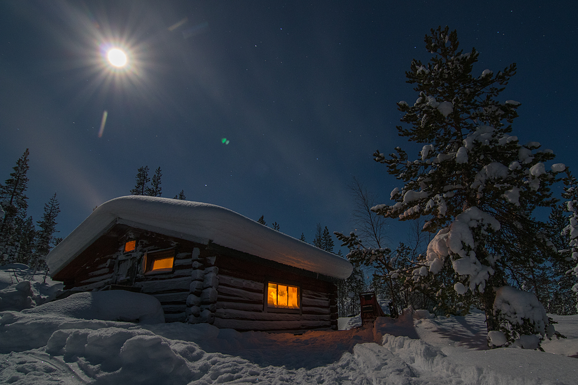 Winter time in Jokkmokk and full moon over a timber hut on a dog sledding tour.