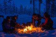 Korvgrillning över öppen eld i skymningsljus. Med hundspann i skogslandet.
