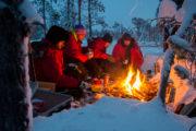 Lunchpaus över öppen eld i skogslandskap på turen Hundspannsäventyr och norrskensnätter vinter lappland.
