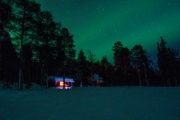 Stila norrsken över röd liten snötäckt stuga. Bild från turen Hundspannsäventyr och norrskensnätter.