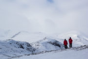 Two persons admiring the view over mountain valley in winter. Picture from the dog sled adventure called A Taste of Sarek