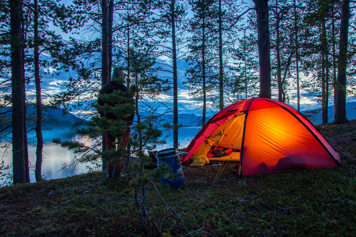 Lit Hilleberg tent in summer Swedish Lapland. Canoeing in the Pearl river Nature Reserve with Jokkmokkguiderna.