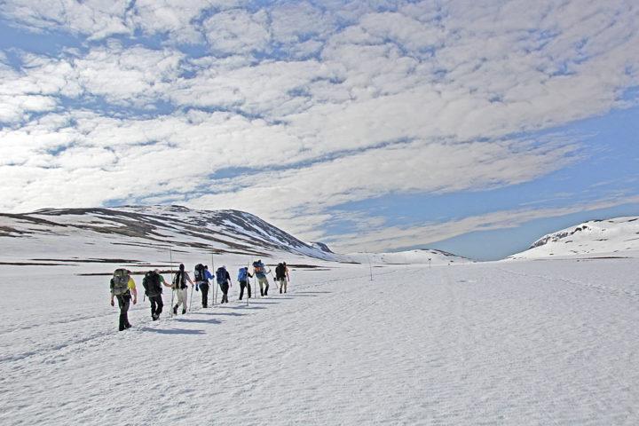 Tjäktja snow in summer. Hikers on snow. King's trail.