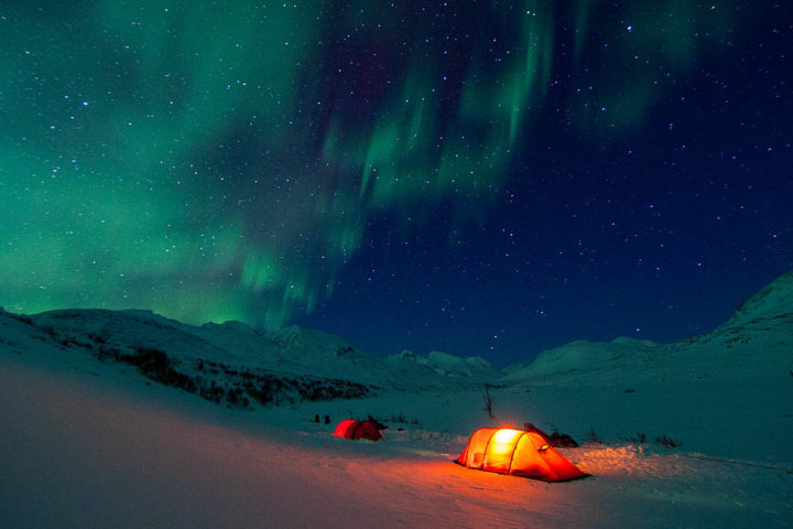 Northern light in Rapadalen Sarek National Park. Red tents and green snow.
