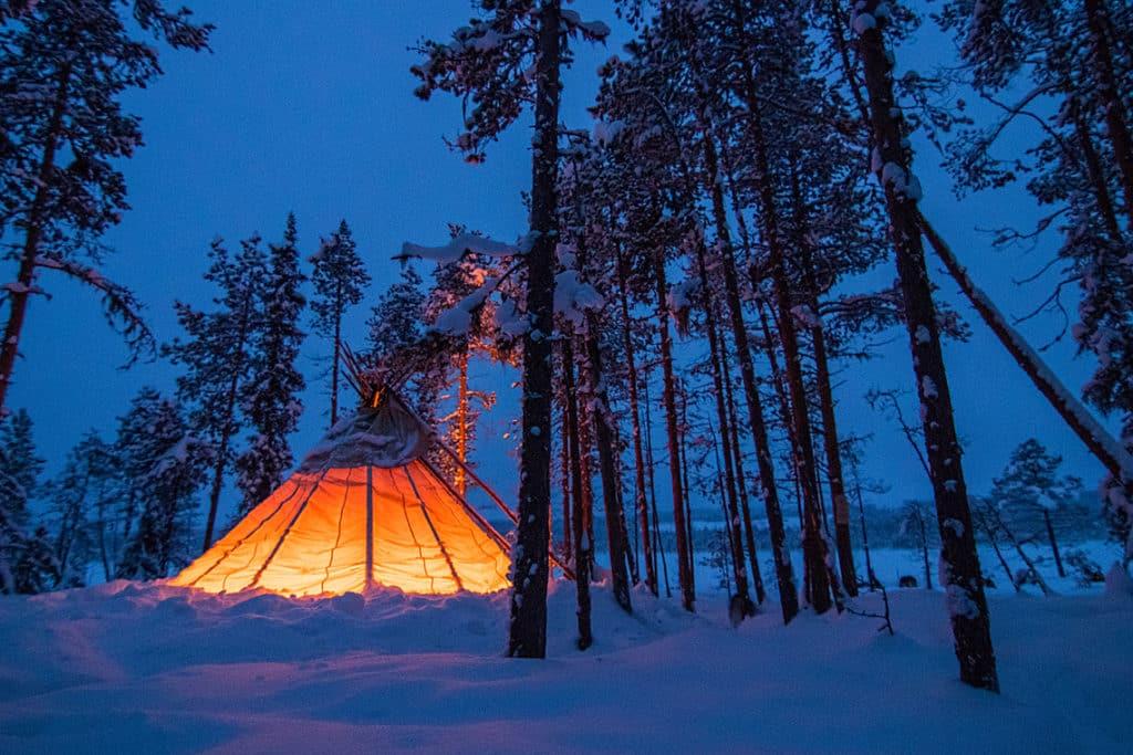 upplyst tältkåta i Jokkmokks skogar. Bild från Norrskenstur med hundspann.